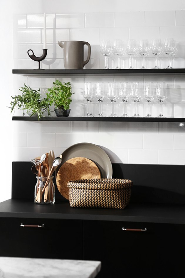 A kitchen with black shelves and countertops.