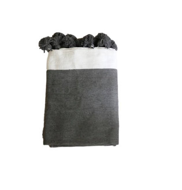 Gray throw blanket with pom poms and white border