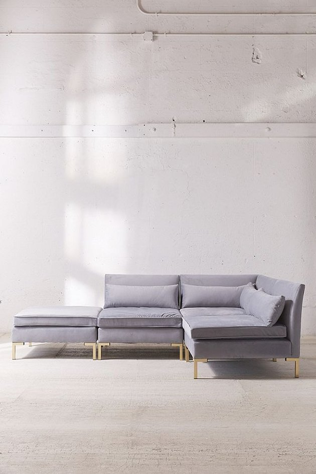 L-shaped lavender couch with brass legs