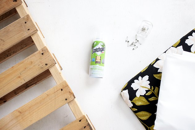 Picture of supplies of pallet wood, outdoor cushion, fabric, fabric water shield spray and safety pins.