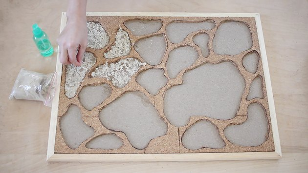 Adding moss adhesive to holes in bulletin board
