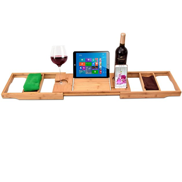 Blonde wood bathtub tray displaying tablet, wine and washcloths