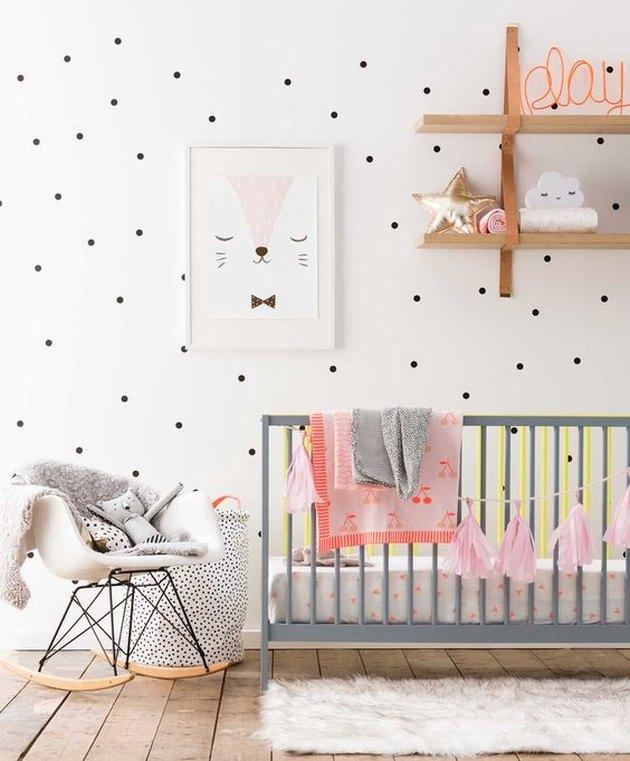 nursery with polka dot walls and grey crib
