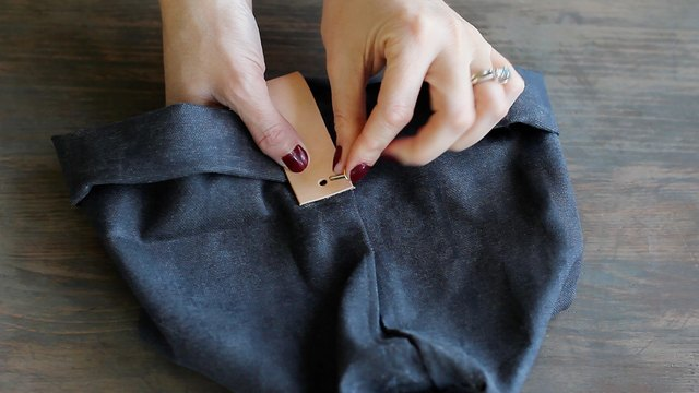 Inserting brass rivet post through hole of leather strip