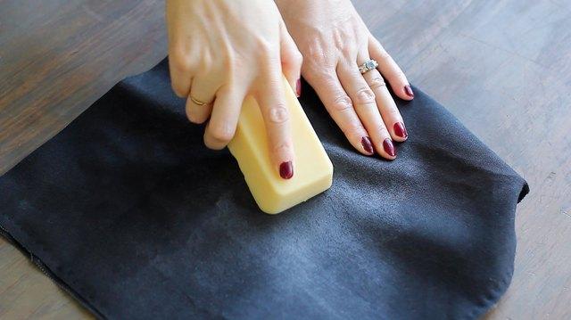 Rubbing bar of fabric wax into canvas fabric