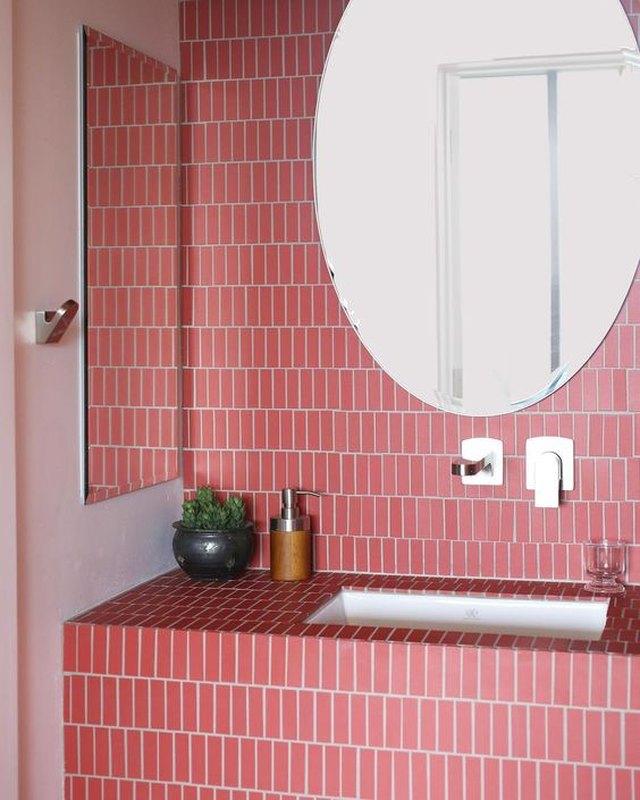 carreau de céramique rose sur le mur et la vanité de la salle de bain