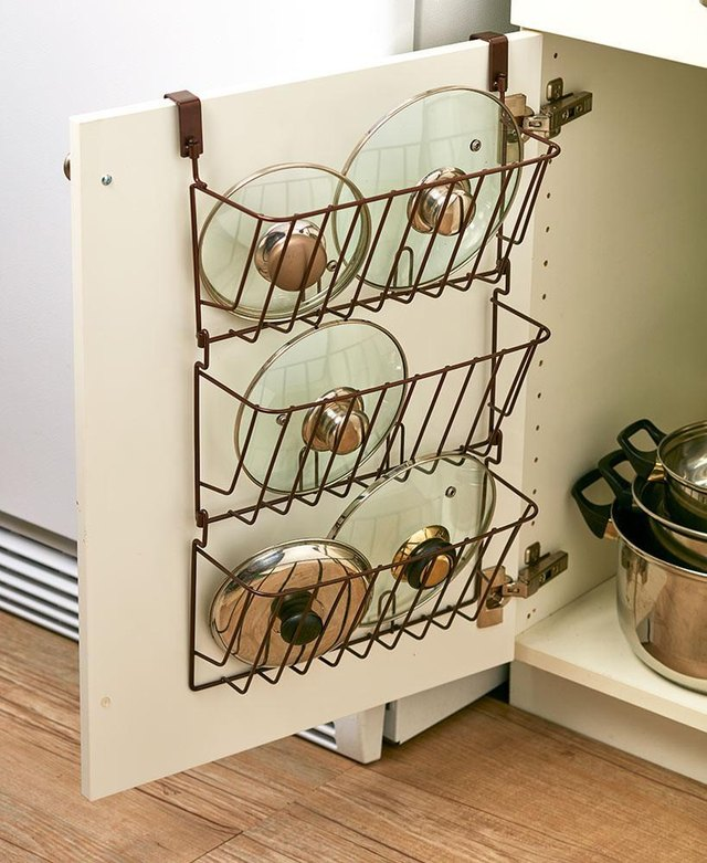 A hanging rack on an inside cupboard door stores lids for pots and pans.