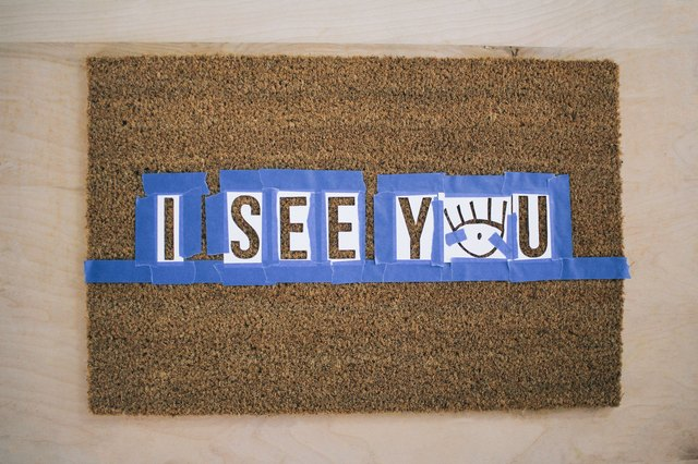 Letter stencils taped to doormat