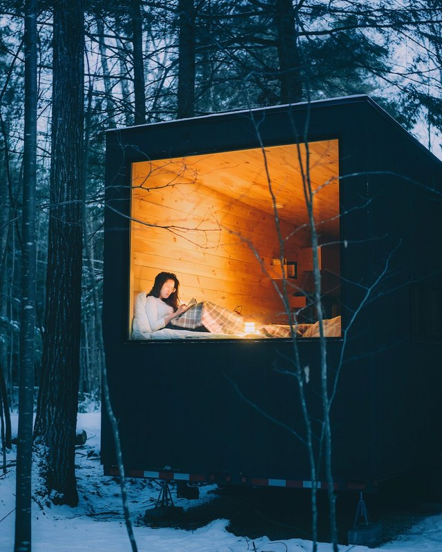 Girl reading in tiny snow-surrounded cabin.