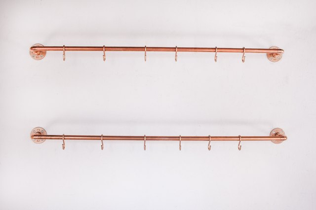 Two copper pipes with S hooks mounted on wall