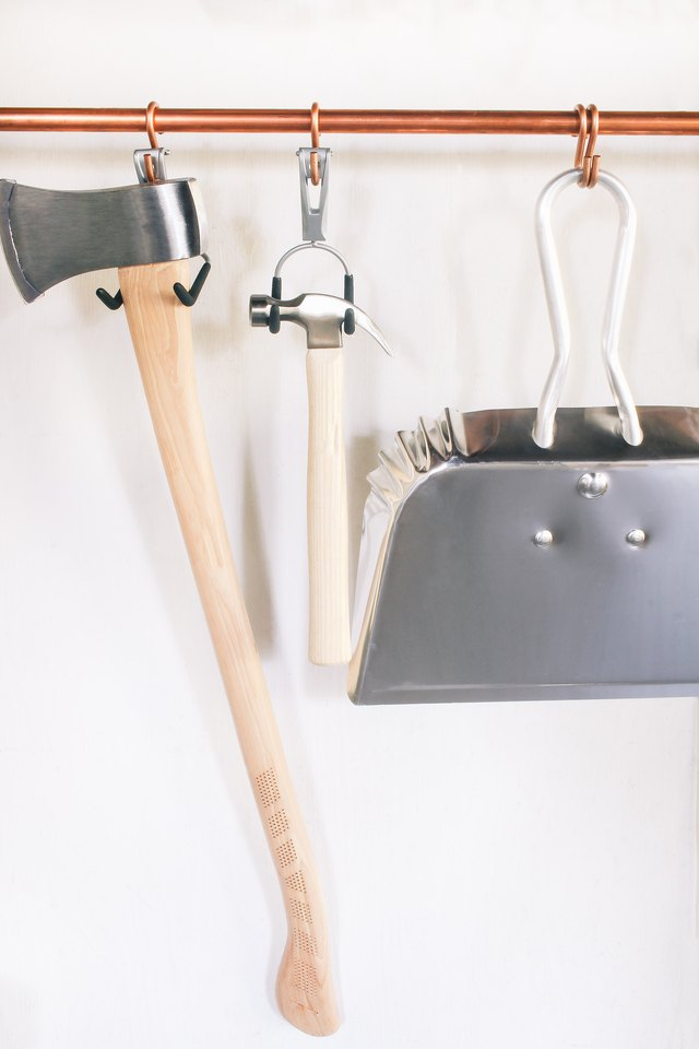 Axe, hammer and dustpan hung on copper pipe with utility hooks
