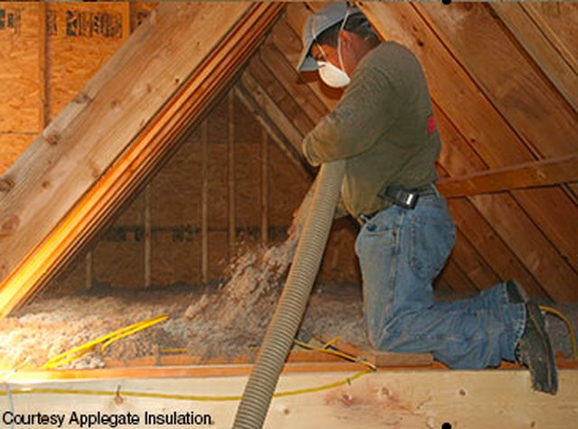 Blowing insulation into an attic.