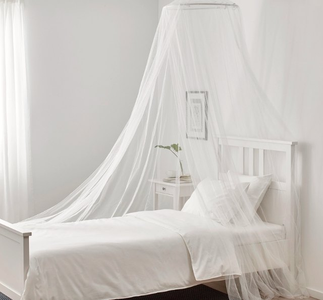white mosquito netting over bed