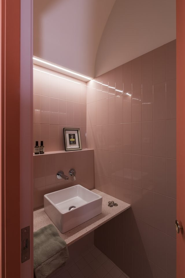 pink bathroom with dramatic lighting and floating vanity