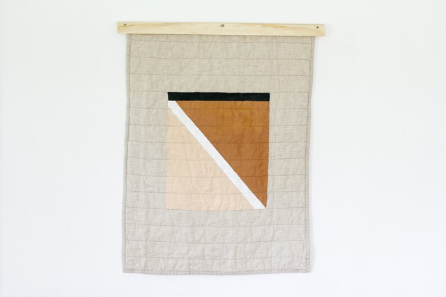 painted quilt hanging displayed on quilt hanger