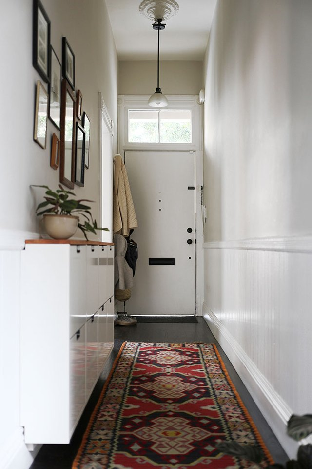 narrow hallway with area rug, storage cabinet, and pendant light