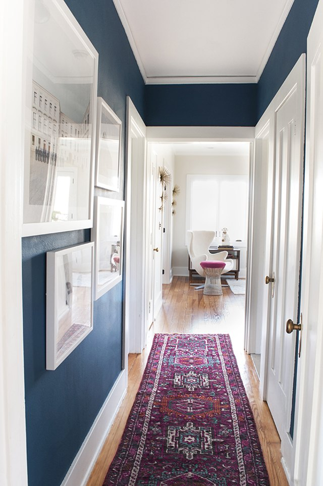 narrow hallway with area rug and gallery wall