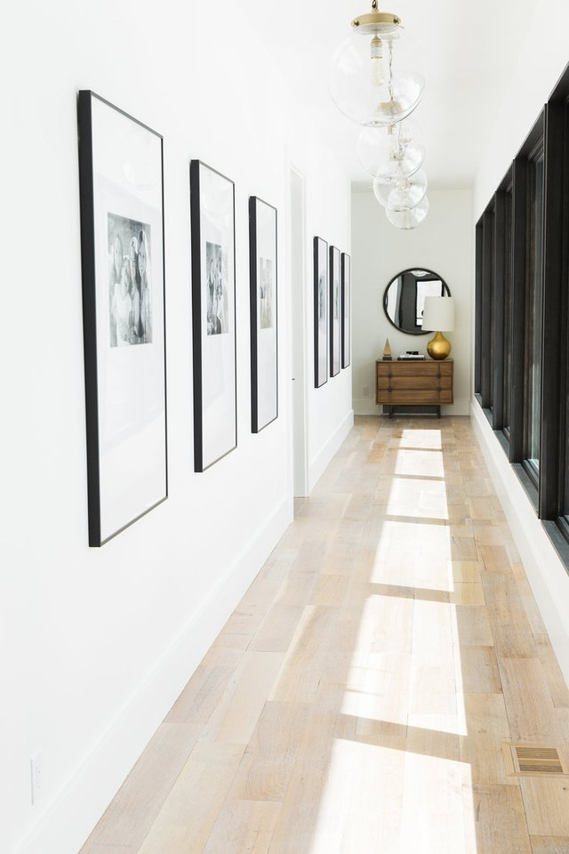 long narrow hallway with pendant lighting and console table
