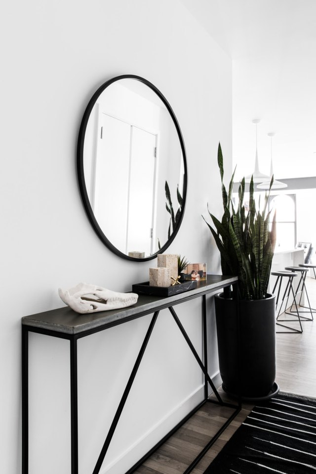 narrow console table in hallway with round mirror and area rug
