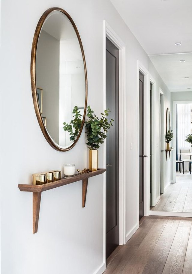 round mirror in hallway above wall-mounted shelf