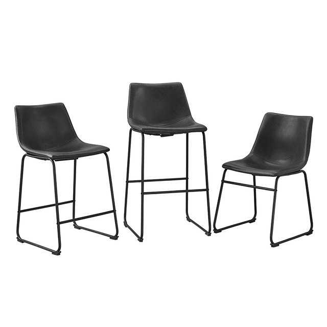 Three faux leather minimal armless black dining chairs at various heights