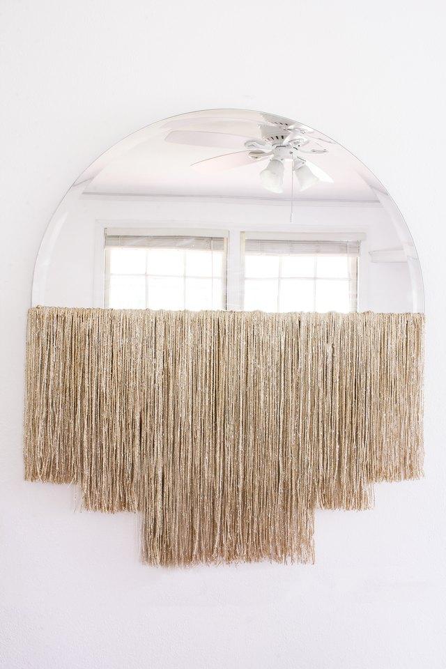 DIY fringe mirror hanging on wall