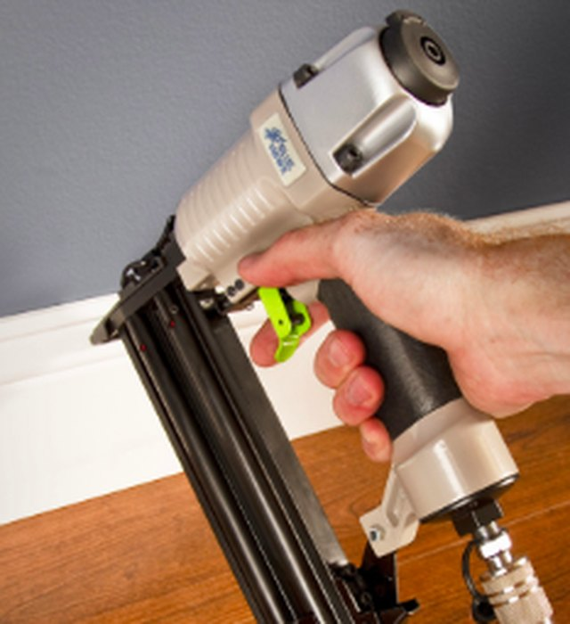 Installing baseboards with a nailer.
