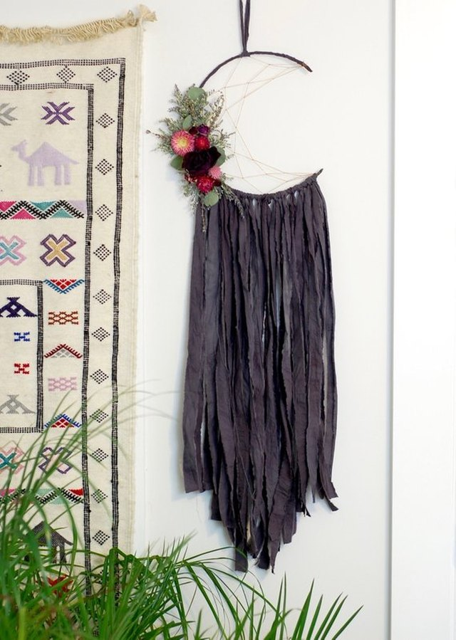 Moon-shaped dreamcatcher with dark grey fringe and dried flower accent