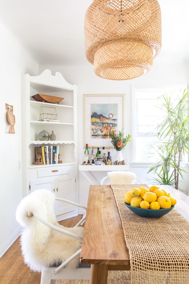 white dining room with woven rattan pendant light