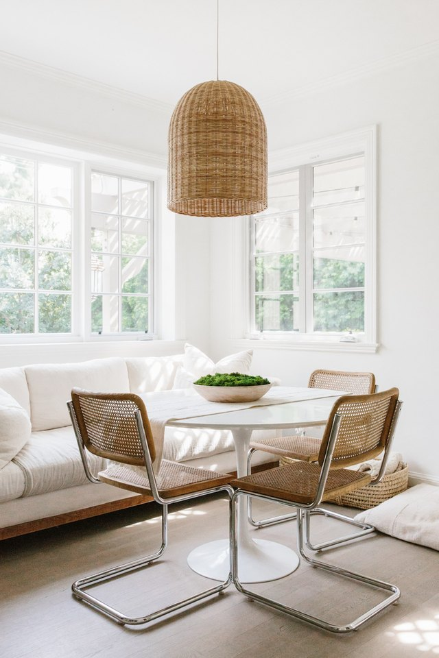 white dining room with cane dining chairs and bell-shaped pendant