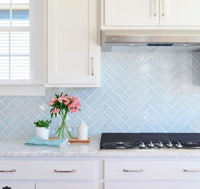 white kitchen with light-blue herringbone tile backsplash