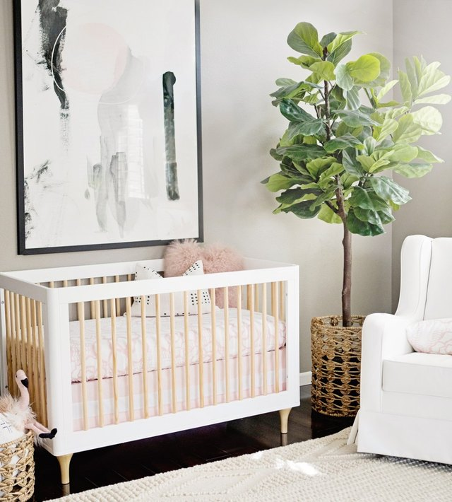 pink and white nursery with modern crib upholstered rocker and fiddle leaf fig tree