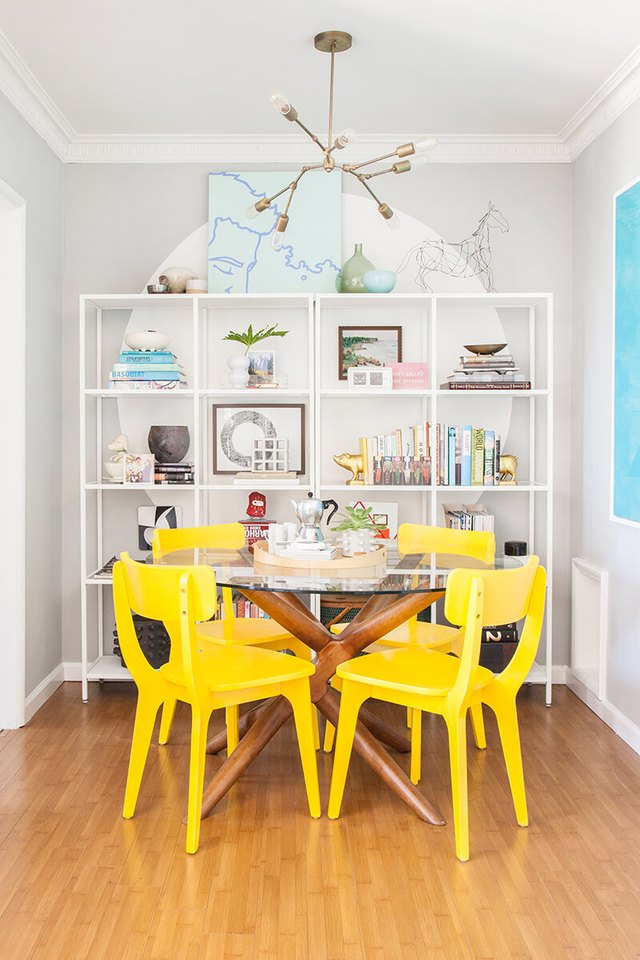 small dining room  with glass top dining table and yellow dining chairs