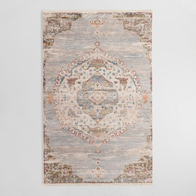 Faded Persian-style rug featuring beige, light gray, and pale peach hues