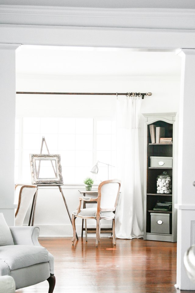 An easel set up in a breezy white living room framed by window