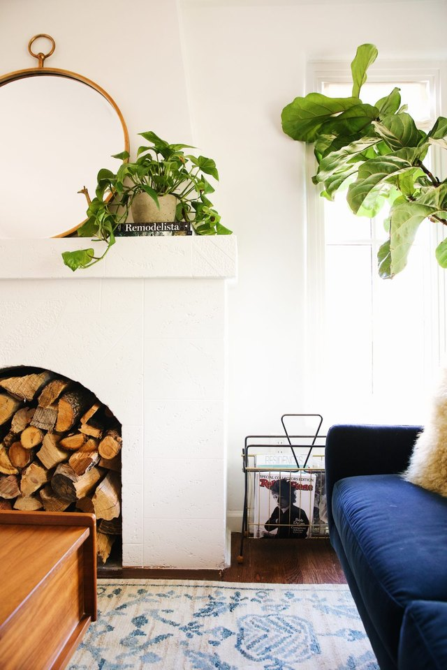 white living room with green plants and stacked wood