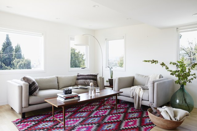 white living room with colorful geometric pattern area rug