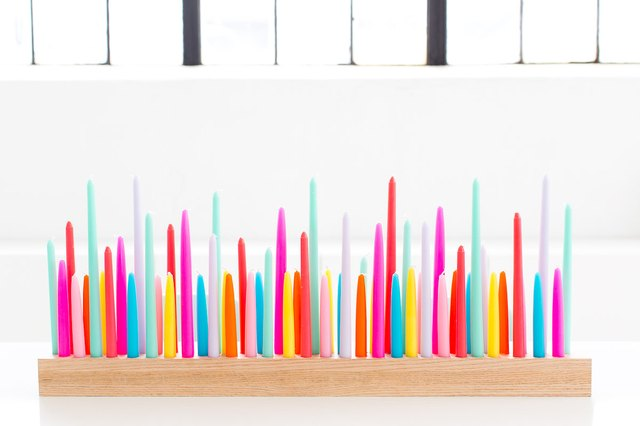 Colorful neon candles in a wooden holder