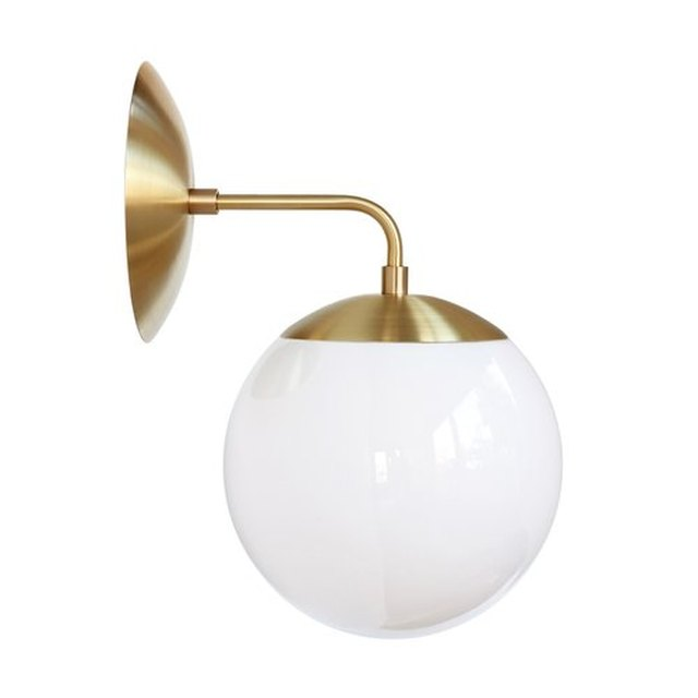 L-shaped brass sconce with white globe light