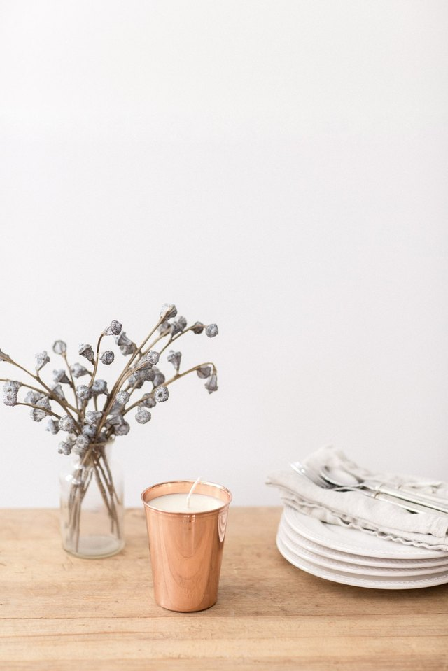 candle in a copper tumbler