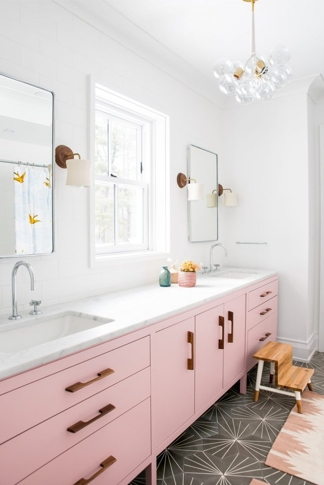 A bathroom with pink cabinetry