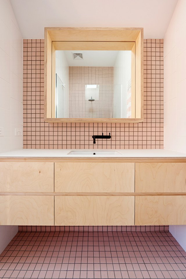 bathroom with pink mosaic tile and floating vanity
