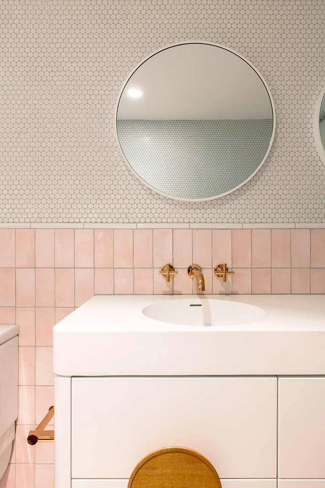 bathroom with pink tile wainscot and round penny tile