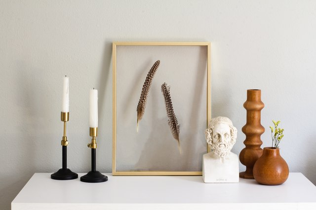 Target Decor: Black and gold candlesticks, framed feathers, and wood vases on entry table
