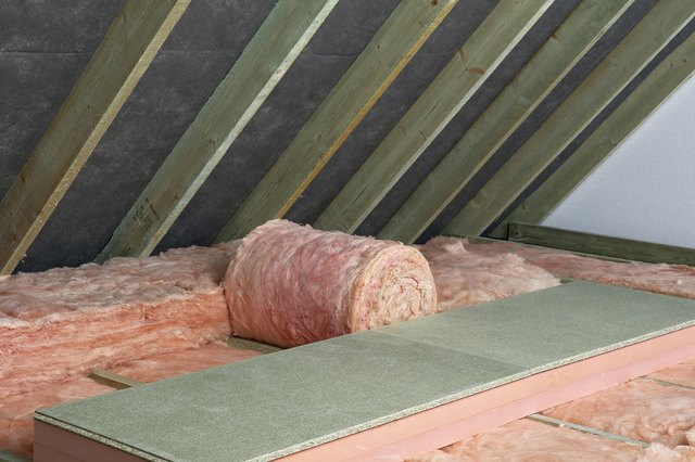 Storage decking on top of fiberglass roof insulating material in attic