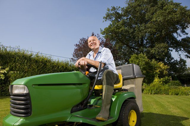 Senior man sitting on riding lawn mower
