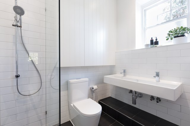 Small ensuite bathroom with tiling laid in a brick pattern