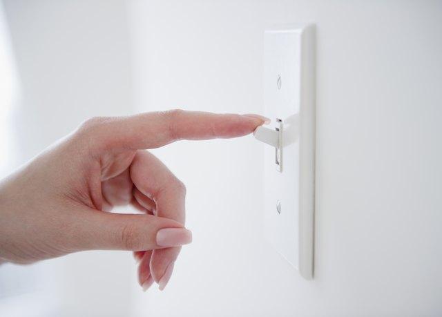 Korean woman turning off light switch