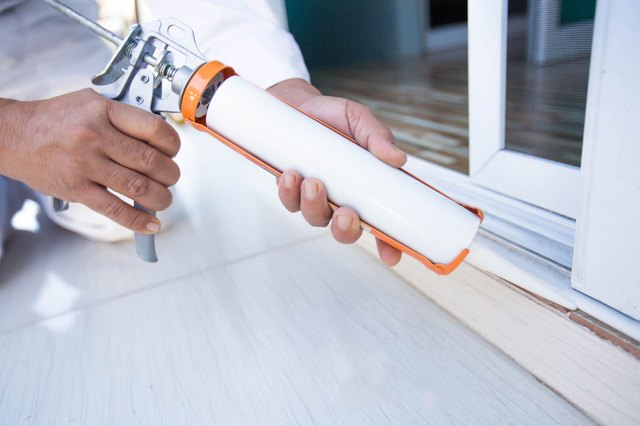 Construction workers install doors - windows and use silicon and sealant.