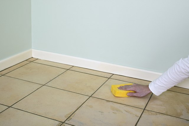 Man using sponge to clean grout off tiled floor in room